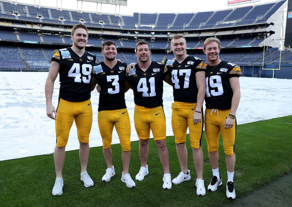 Iowa Hawkeyes linebacker Nick Niemann (49), place kicker Keith Duncan (3), defensive back Colton Dinsdale (41), linebacker Nick Anderson (47), and wide receiver Max Cooper (19) following the team photo Wednesday, December 25, 2019 at SDCCU Stadium in San Diego. (Brian Ray/hawkeyesports.com)