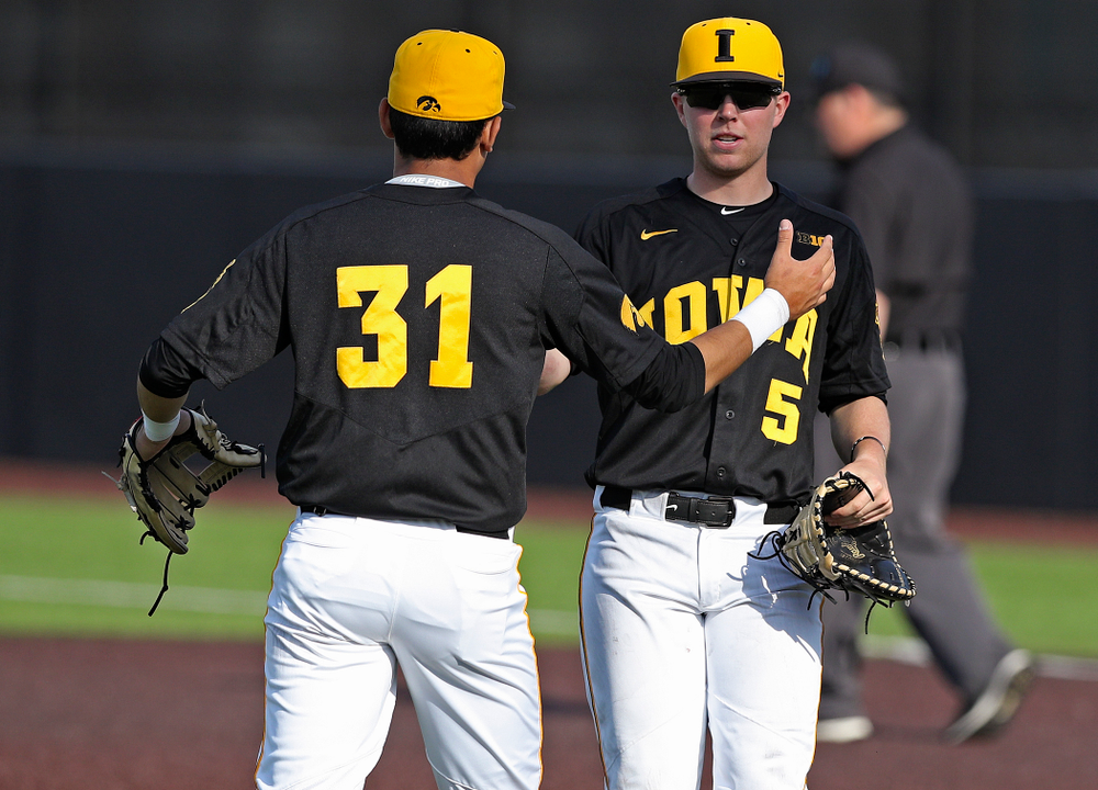 Iowa Hawkeyes third baseman Matthew Sosa (31) and first baseman Zeb Adreon (5) celebrate after winning their game against Rutgers at Duane Banks Field in Iowa City on Saturday, Apr. 6, 2019. (Stephen Mally/hawkeyesports.com)