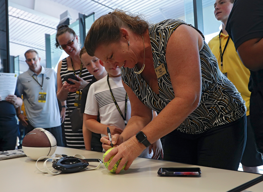 2019 University of Iowa Athletics Hall of Fame inductee Diane Pohl signs a softball at the University of Iowa Athletics Hall of Fame in Iowa City on Friday, Aug 30, 2019. (Stephen Mally/hawkeyesports.com)