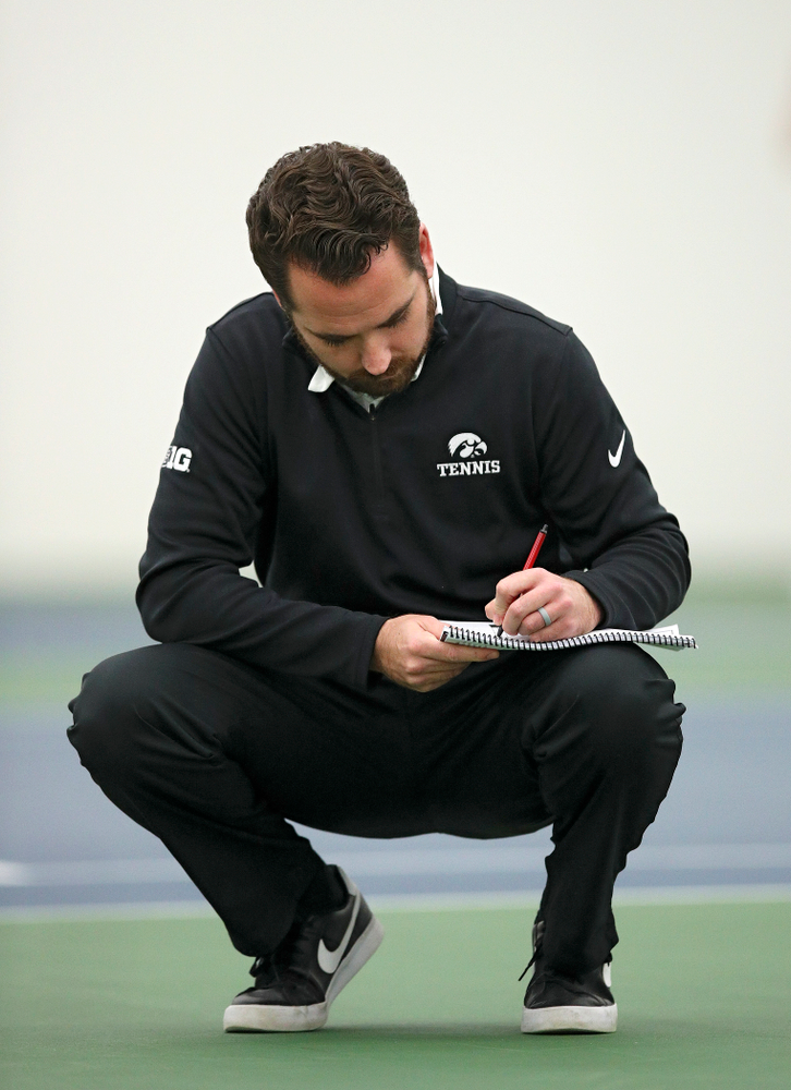 Iowa head coach Ross Wilson takes notes during their match at the Hawkeye Tennis and Recreation Complex in Iowa City on Thursday, January 16, 2020. (Stephen Mally/hawkeyesports.com)