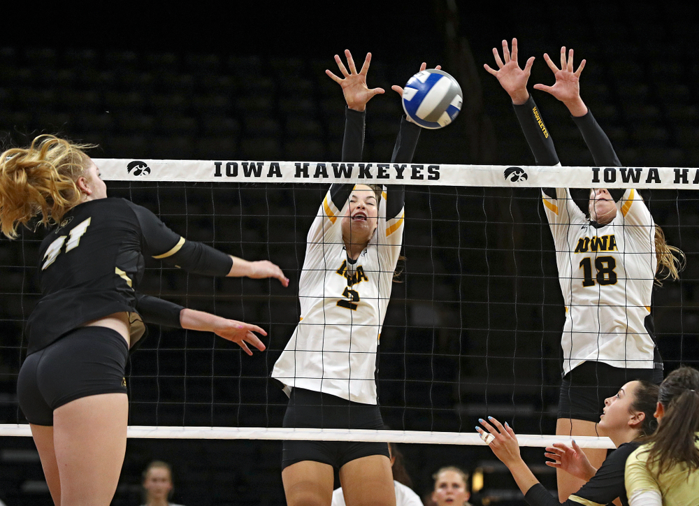 Iowa's Courtney Buzzerio (2) and Hannah Clayton (18) try for a block during the third set of their Big Ten/Pac-12 Challenge match against Colorado at Carver-Hawkeye Arena in Iowa City on Friday, Sep 6, 2019. (Stephen Mally/hawkeyesports.com)