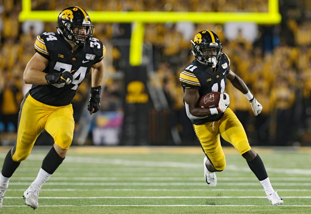 Iowa Hawkeyes defensive back Michael Ojemudia (11) runs after intercepting a pass as linebacker Kristian Welch (34) looks to block during the fourth quarter of their game at Kinnick Stadium in Iowa City on Saturday, Aug 31, 2019. (Stephen Mally/hawkeyesports.com)