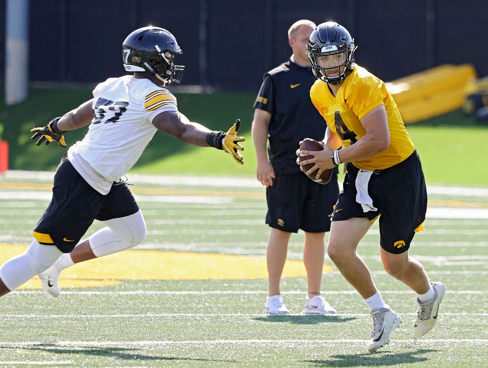 Iowa Hawkeyes quarterback Nate Stanley (4) steps up to avoid defensive end Chauncey Golston (57) during Fall Camp Practice No. 13 at the Hansen Football Performance Center in Iowa City on Friday, Aug 16, 2019. (Stephen Mally/hawkeyesports.com)