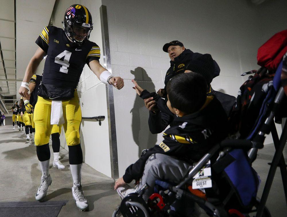Iowa Hawkeyes quarterback Nate Stanley (4) fist bumps Kid Captain Mason Gonzalez before a game against Northwestern at Kinnick Stadium on November 10, 2018. (Tork Mason/hawkeyesports.com)