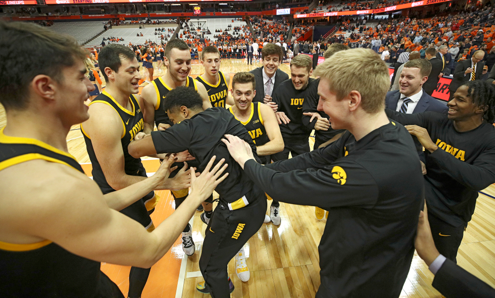 Iowa Hawkeyes guard Jordan Bohannon (3), forward Riley Till (20), and center Luka Garza (55) celebrate after winning their ACC/Big Ten Challenge game at the Carrier Dome in Syracuse, N.Y. on Tuesday, Dec 3, 2019. (Stephen Mally/hawkeyesports.com)
