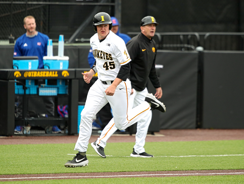 Iowa first baseman Peyton Williams (45) runs past head coach Rick Heller as he scores a run during the first inning of their college baseball game at Duane Banks Field in Iowa City on Wednesday, March 11, 2020. (Stephen Mally/hawkeyesports.com)