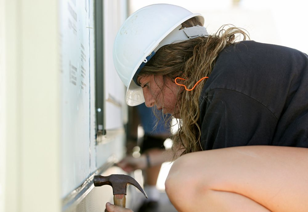 Iowa's McKenna Warnock hammers in a nail on a piece of siding as they work on a Habitat for Humanity Women Build project in Iowa City on Wednesday, Sep 25, 2019. (Stephen Mally/hawkeyesports.com)