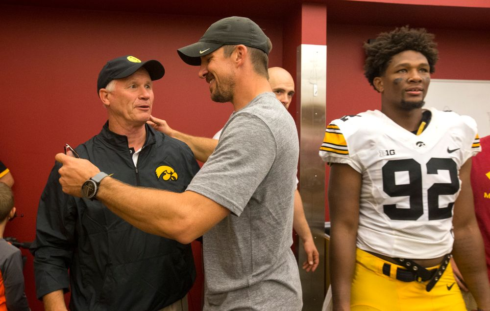 Former Iowa Hawkeyes tight end Dallas Clark talks with defensive line coach Reese Morgan as they celebrate their victory over the Iowa State Cyclones in the Iowa Corn Cy-Hawk Series Saturday, Sept. 12, 2015 at the Jack Trice Stadium in Ames.  (Brian Ray/hawkeyesports.com)