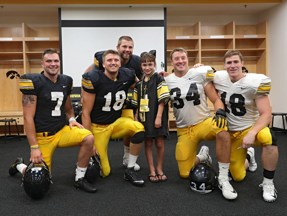 Kid Captain Aubrey Bussan-Kluesner takes a picture with Iowa football players during Kids Day at Kinnick Stadium in Iowa City on Saturday, Aug 10, 2019. (Stephen Mally/hawkeyesports.com)