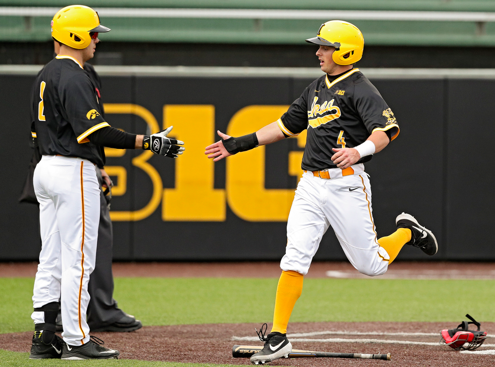 Iowa Hawkeyes second baseman Mitchell Boe (4) gets a high-five from designated hitter Luke Farley (8) after Boe scored a run during the third inning of their game against Illinois State at Duane Banks Field in Iowa City on Wednesday, Apr. 3, 2019. (Stephen Mally/hawkeyesports.com)