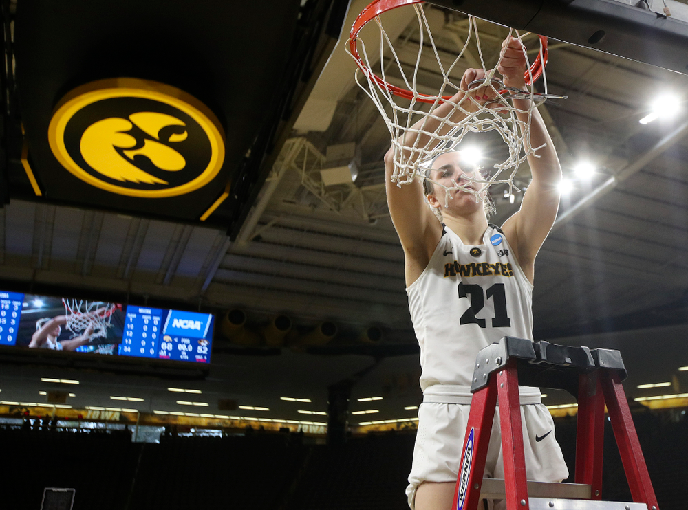 Iowa Hawkeyes forward Hannah Stewart (21) cuts down the net after winning their second round game in the 2019 NCAA Women's Basketball Tournament at Carver Hawkeye Arena in Iowa City on Sunday, Mar. 24, 2019. (Stephen Mally for hawkeyesports.com)