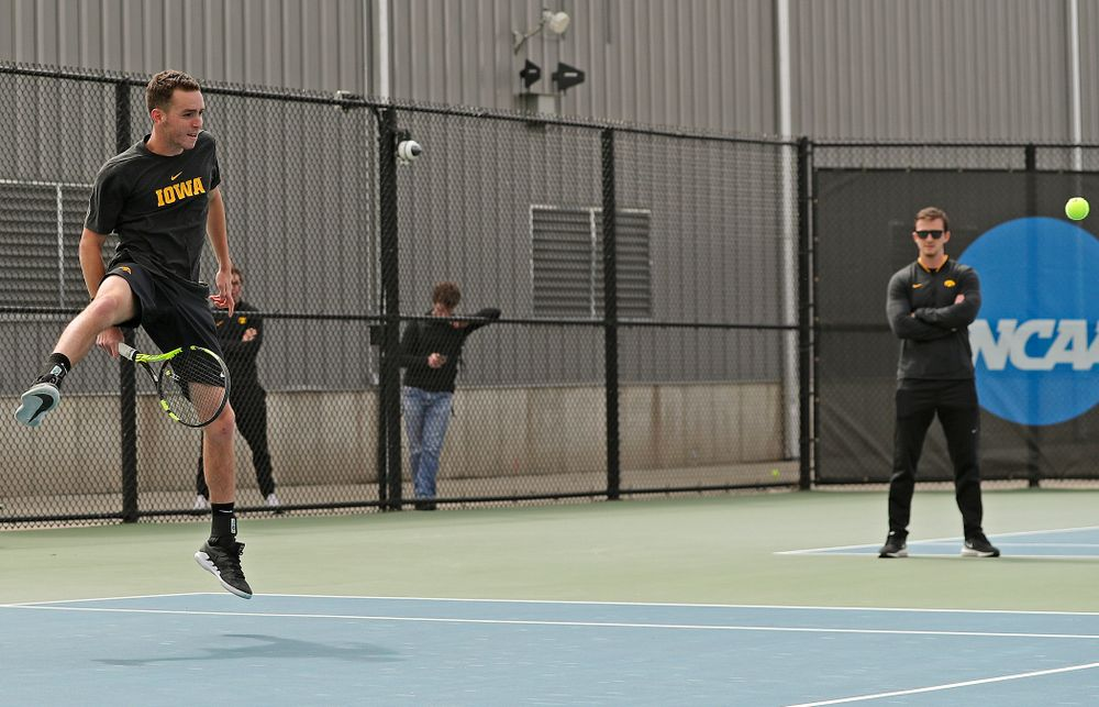 Iowa's Kareem Allaf hits a shot between his legs during a double match against Ohio State at the Hawkeye Tennis and Recreation Complex in Iowa City on Sunday, Apr. 7, 2019. (Stephen Mally/hawkeyesports.com)