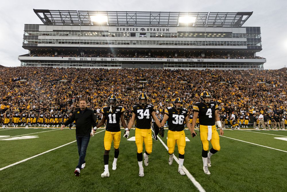 Honorary captain Bob Stopps with captains defensive back Michael Ojemudia (11), linebacker Kristian Welch (34), fullback Brady Ross (36), and quarterback Nate Stanley (4) before their game against the Miami RedHawks Saturday, August 31, 2019 at Kinnick Stadium in Iowa City. (Brian Ray/hawkeyesports.com)
