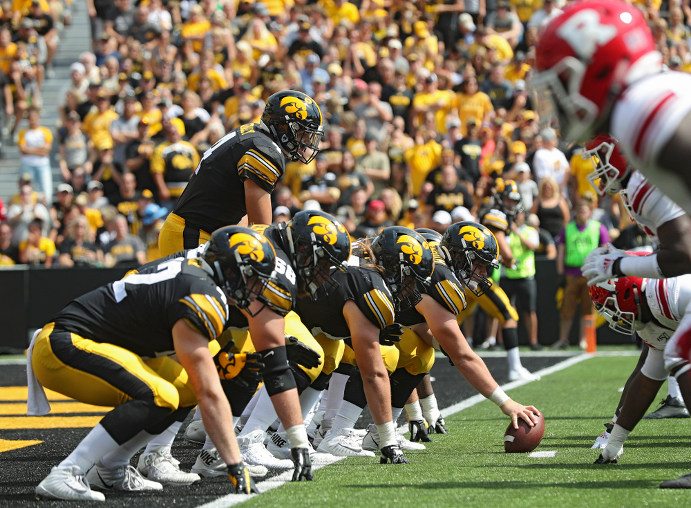 Iowa Hawkeyes quarterback Nate Stanley (4) prepares for a snap from offensive lineman Tyler Linderbaum (65) during the third quarter of their Big Ten Conference football game at Kinnick Stadium in Iowa City on Saturday, Sep 7, 2019. (Stephen Mally/hawkeyesports.com)