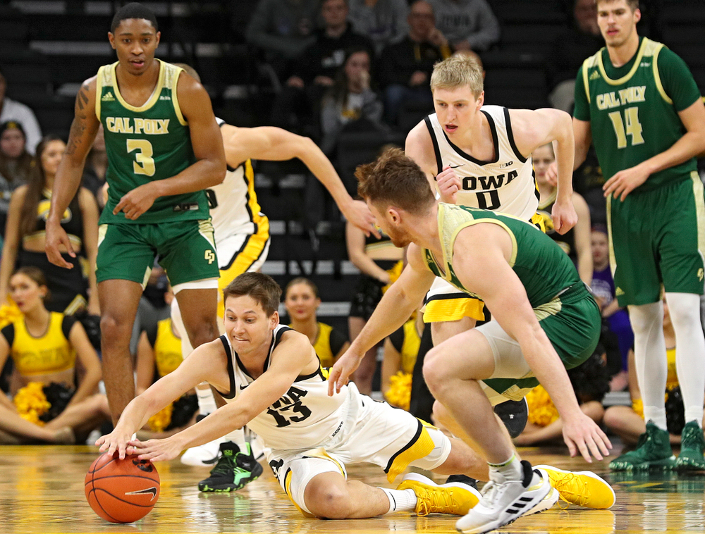 Iowa Hawkeyes guard Austin Ash (13) dives for a loose ball on the floor during the second half of their game at Carver-Hawkeye Arena in Iowa City on Sunday, Nov 24, 2019. (Stephen Mally/hawkeyesports.com)