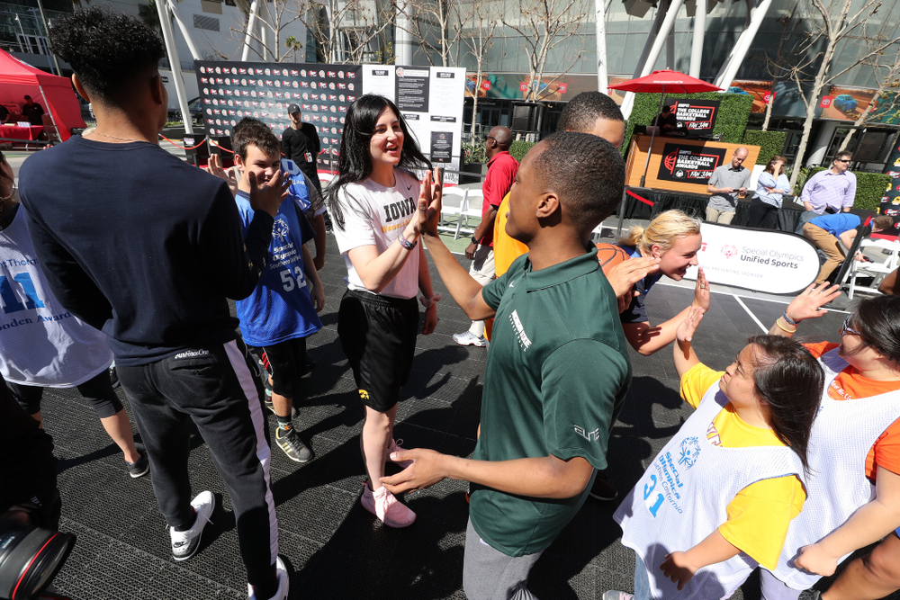 Iowa Hawkeyes forward Megan Gustafson (10) high fives Michigan StateÕs Cassius Winston during a Special Olympics event Friday, April 12, 2019 as part of the ESPN College Basketball Awards in the XBOX Plaza at LA Live.  (Brian Ray/hawkeyesports.com)