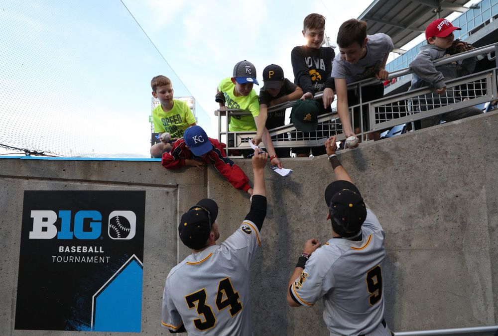 Iowa Hawkeyes catcher Austin Martin (34) and outfielder Ben Norman (9) sign autographs following their game against the Indiana Hoosiers in the first round of the Big Ten Baseball Tournament Wednesday, May 22, 2019 at TD Ameritrade Park in Omaha, Neb. (Brian Ray/hawkeyesports.com)