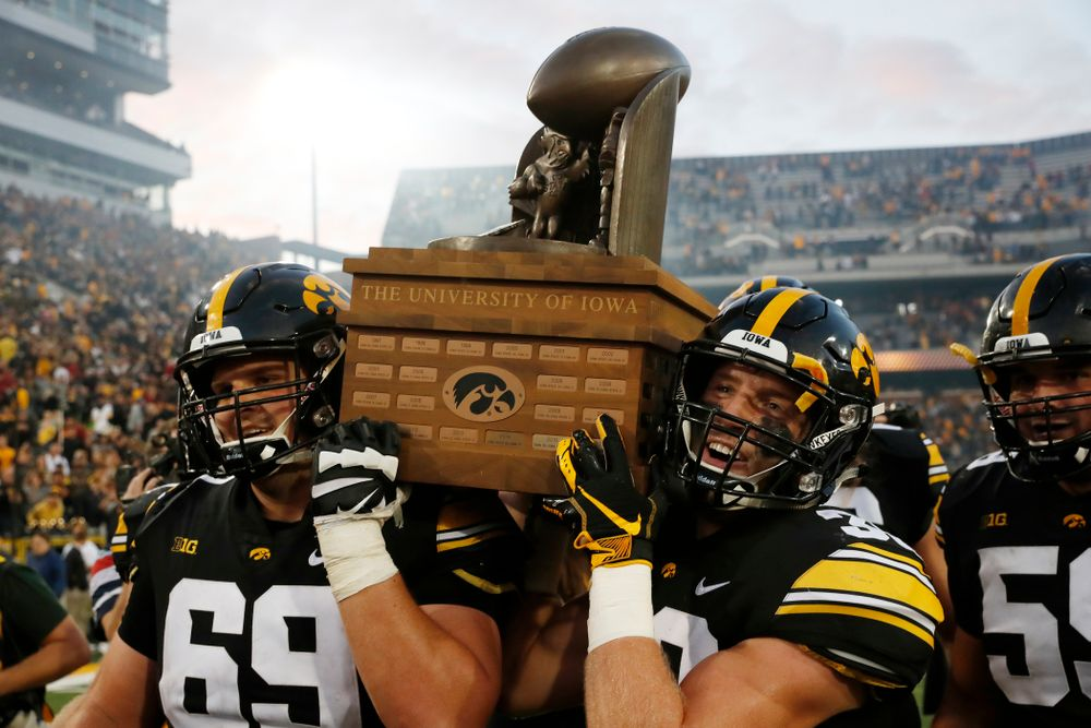 Iowa Hawkeyes offensive lineman Keegan Render (69) and defensive back Jake Gervase (30) celebrate with the Cy-Hawk trophy following their game against the Iowa State Cyclones Saturday, September 8, 2018 at Kinnick Stadium. (Brian Ray/hawkeyesports.com)