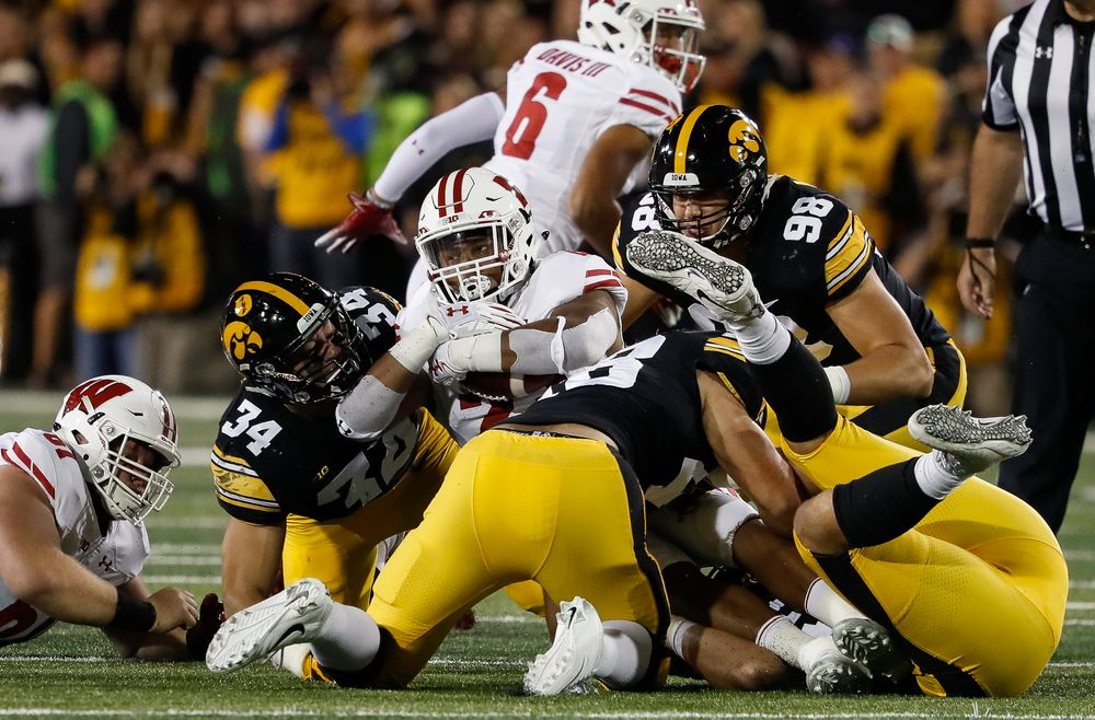 Iowa Hawkeyes linebacker Kristian Welch (34), Iowa Hawkeyes linebacker Jack Hockaday (48), and Iowa Hawkeyes defensive end Anthony Nelson (98) make a tackle during a game against Wisconsin at Kinnick Stadium on September 22, 2018. (Tork Mason/hawkeyesports.com)