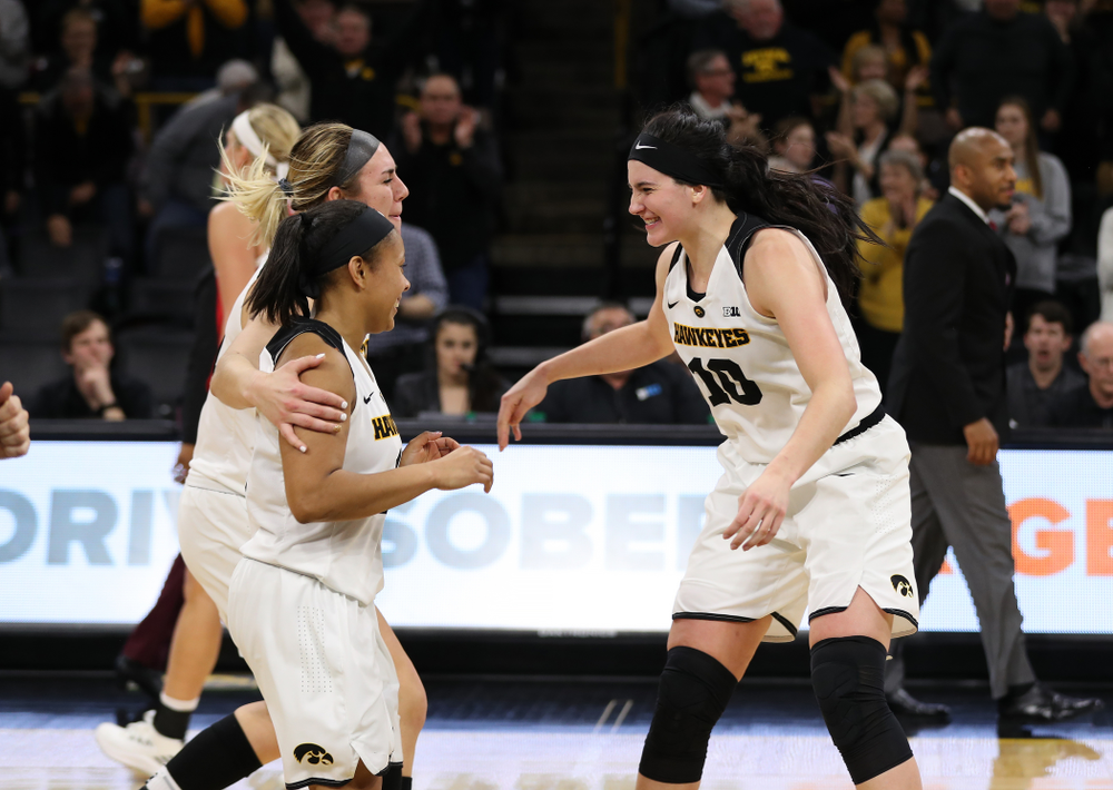 Iowa Hawkeyes forward Megan Gustafson (10), forward Hannah Stewart (21), and guard Tania Davis (11) celebrate their victory against the Nebraska Cornhuskers Thursday, January 3, 2019 at Carver-Hawkeye Arena. (Brian Ray/hawkeyesports.com)