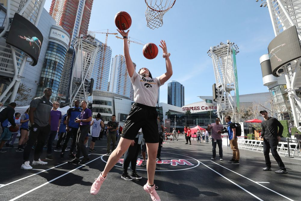 Iowa Hawkeyes forward Megan Gustafson (10) does the Mikan drill as DukeÕs Zion Williamson and RJ Barrett look on during a Special Olympics event Friday, April 12, 2019 as part of the ESPN College Basketball Awards in the XBOX Plaza at LA Live.  (Brian Ray/hawkeyesports.com)