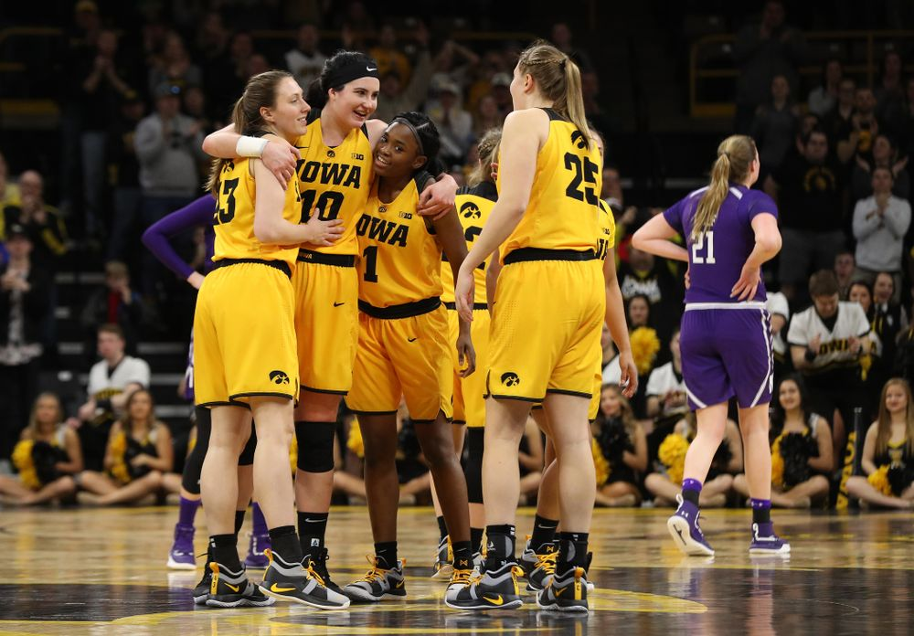 Iowa Hawkeyes forward Megan Gustafson (10) hugs forward Amanda Ollinger (43), and guard Tomi Taiwo (1) as she lives the court for the final time against the Northwestern Wildcats Sunday, March 3, 2019 at Carver-Hawkeye Arena. (Brian Ray/hawkeyesports.com)