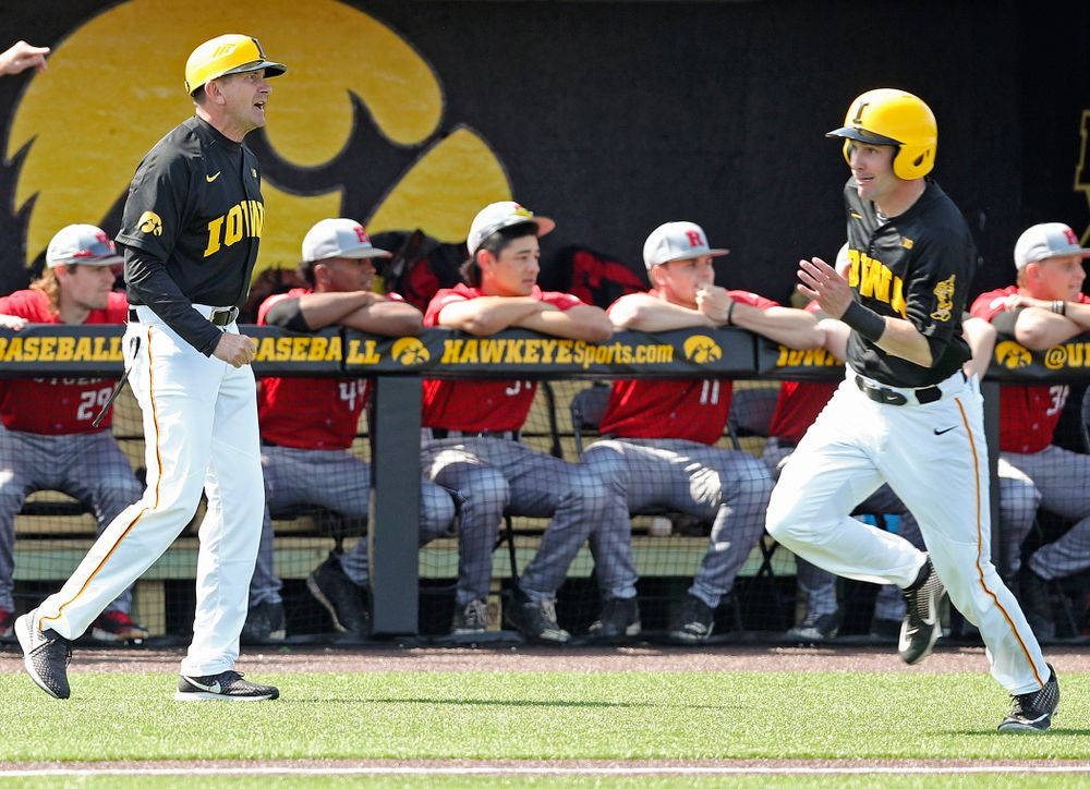Iowa Hawkeyes head coach Rick Heller (from left) looks on as left fielder Chris Whelan (28) runs home to score a run during the first inning of their game against Rutgers at Duane Banks Field in Iowa City on Saturday, Apr. 6, 2019. (Stephen Mally/hawkeyesports.com)