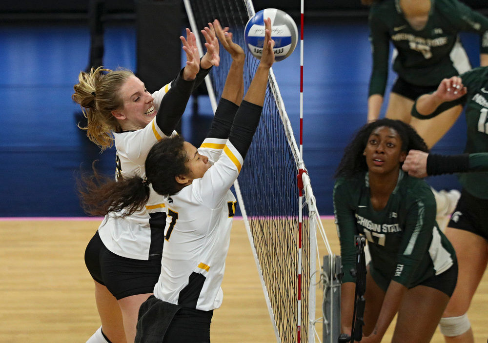 Iowa's Hannah Clayton (18) and Brie Orr (7) block a shot during the third set of their volleyball match at Carver-Hawkeye Arena in Iowa City on Sunday, Oct 13, 2019. (Stephen Mally/hawkeyesports.com)