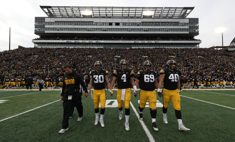 Honorary Captain Jason Baker walks to mid-field with captains Jake Gervase, Nate Stanley, Keegan Render, and Parker Hesse for the coin toss against the Northwestern Wildcats Saturday, November 10, 2018 at Kinnick Stadium. (Brian Ray/hawkeyesports.com)