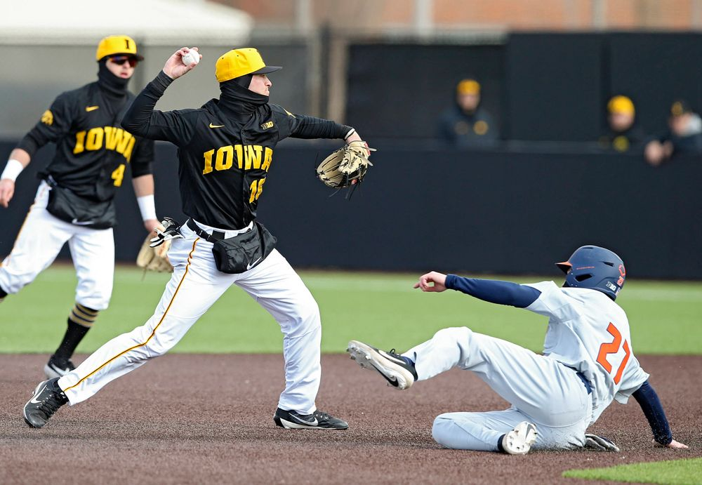 Iowa Hawkeyes shortstop Tanner Wetrich (16) throws to first base for a double play during the sixth inning of their game against Illinois at Duane Banks Field in Iowa City on Saturday, Mar. 30, 2019. (Stephen Mally/hawkeyesports.com)