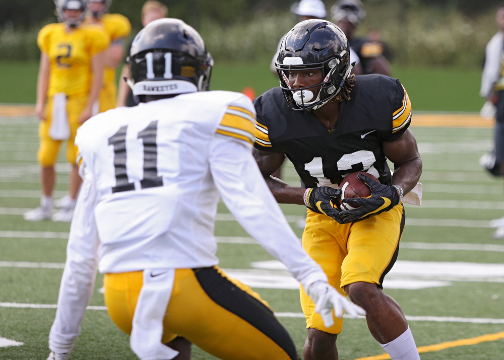 Iowa Hawkeyes wide receiver Brandon Smith (12) tries to avoid defensive back Michael Ojemudia (11) during Fall Camp Practice No. 10 at the Hansen Football Performance Center in Iowa City on Tuesday, Aug 13, 2019. (Stephen Mally/hawkeyesports.com)