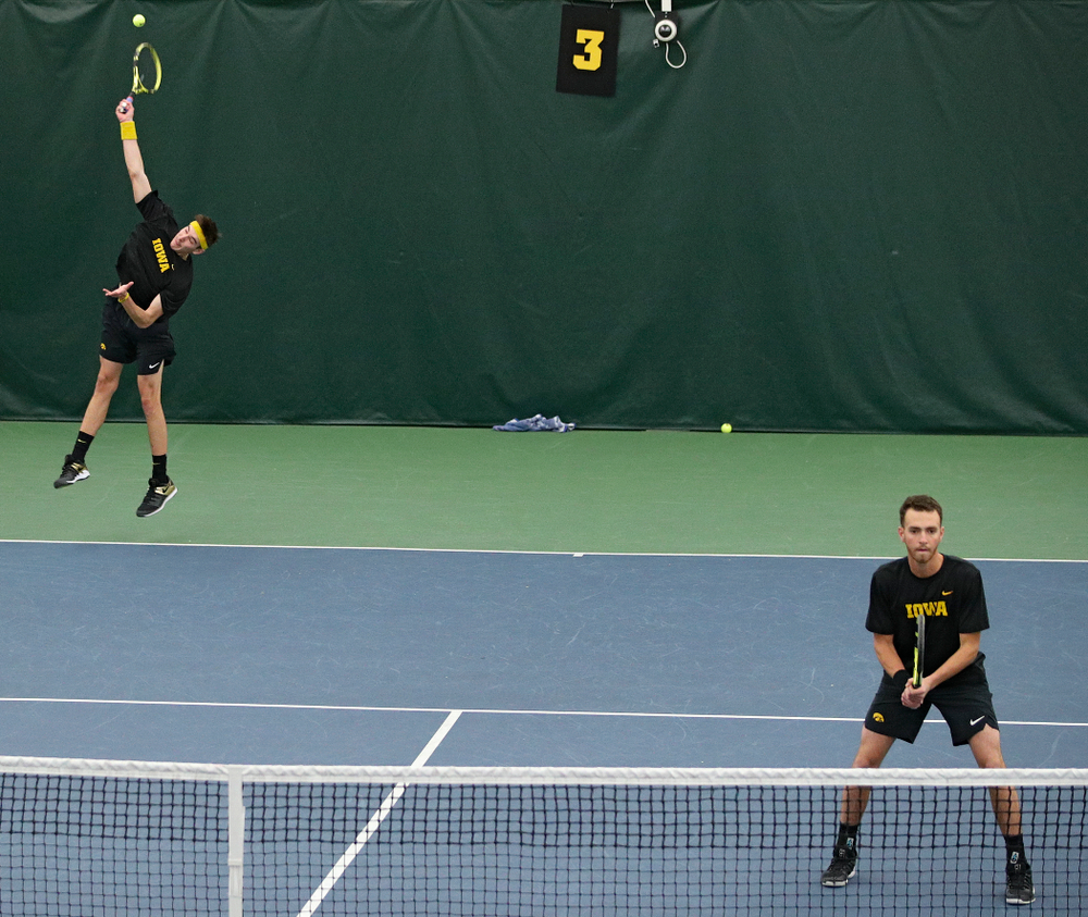 Iowa's Nikita Snezhko (from left) serves as Kareem Allaf waits during their doubles match against Marquette at the Hawkeye Tennis and Recreation Complex in Iowa City on Saturday, January 25, 2020. (Stephen Mally/hawkeyesports.com)