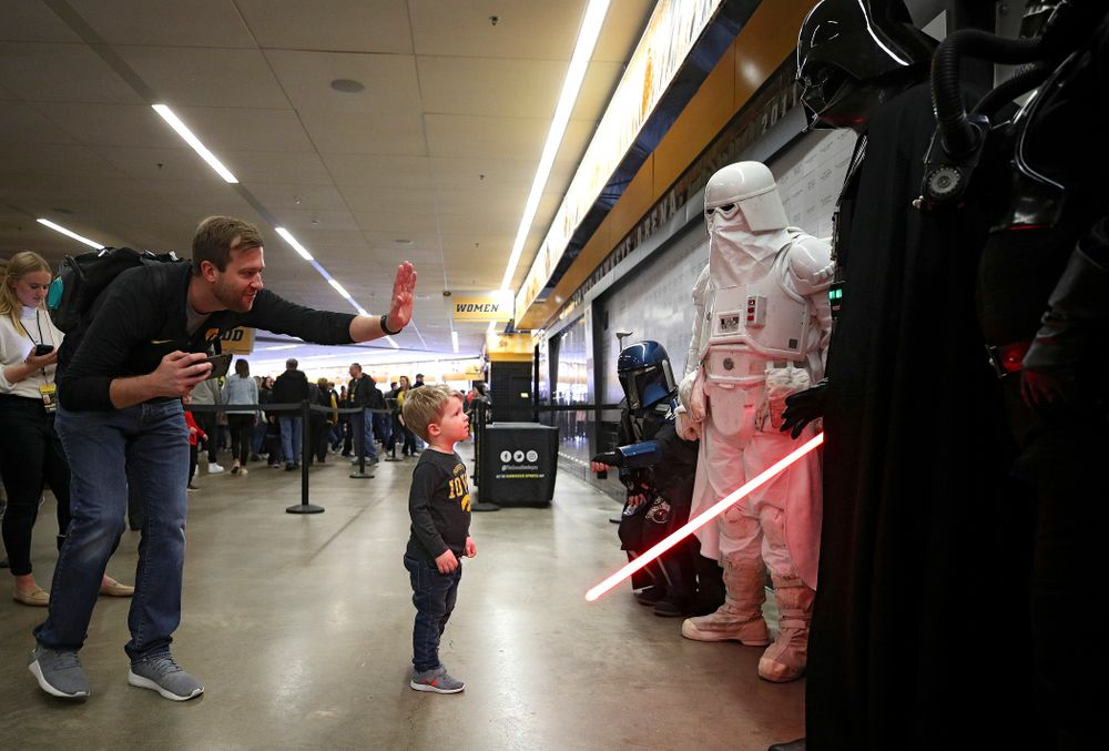 A young Hawkeyes fan gives Darth Vader a high-five on the concourse before the game at Carver-Hawkeye Arena in Iowa City on Sunday, December 29, 2019. (Stephen Mally/hawkeyesports.com)