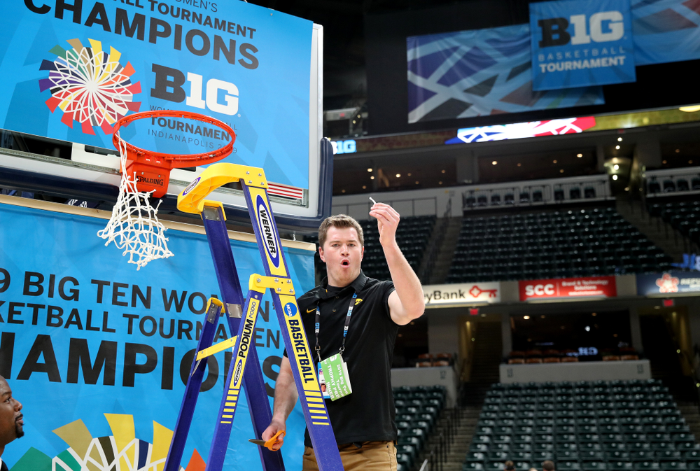 Women's Basketball videographer Zach Grant cuts down the net as they celebrate their victory over the Maryland Terrapins in the Big Ten Championship Game Sunday, March 10, 2019 at Bankers Life Fieldhouse in Indianapolis, Ind. (Brian Ray/hawkeyesports.com)