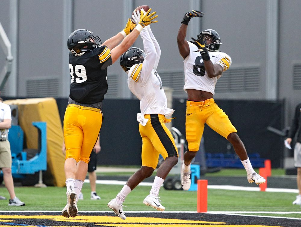 Iowa Hawkeyes defensive back Michael Ojemudia (center) intercepts a pass intended for tight end Nate Wieting (left) after it cleared the hands of defensive back Matt Hankins (8) durning Fall Camp Practice No. 17 at the Hansen Football Performance Center in Iowa City on Wednesday, Aug 21, 2019. (Stephen Mally/hawkeyesports.com)