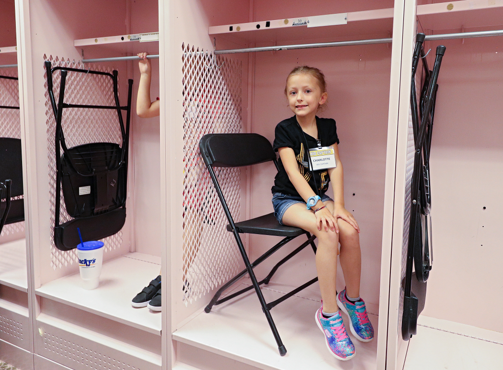Kid Captain Charlotte Keller sits in a locker in the visitor's pink locker room during Kids Day at Kinnick Stadium in Iowa City on Saturday, Aug 10, 2019. (Stephen Mally/hawkeyesports.com)