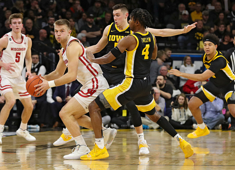 Iowa Hawkeyes guard CJ Fredrick (5) and guard Bakari Evelyn (4) pressure Wisconsin Badgers guard Brad Davison (34) during the first half of their game at Carver-Hawkeye Arena in Iowa City on Monday, January 27, 2020. (Stephen Mally/hawkeyesports.com)