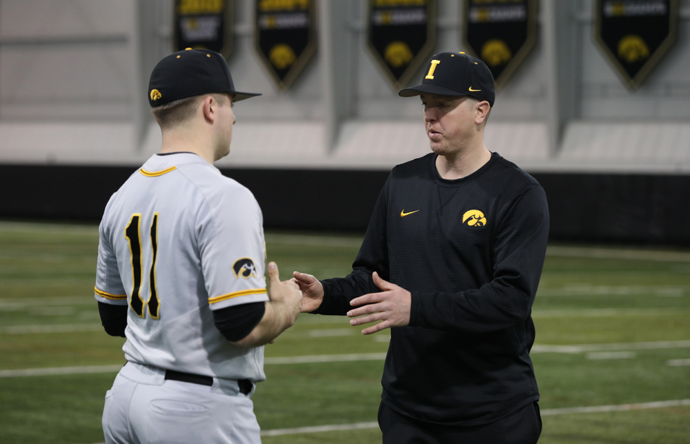 Iowa Hawkeyes Cole McDonald (11) talks with pitching coach Tom Gorzelanny during the team's annual media day Tuesday, February 5, 2019 in the Indoor Practice Facility. (Brian Ray/hawkeyesports.com)