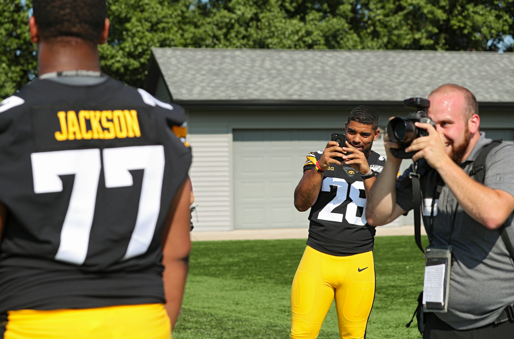 Iowa Hawkeyes running back Toren Young (28) takes a picture of offensive lineman Alaric Jackson (77) as he poses for a portrait during Iowa Football Media Day at the Hansen Football Performance Center in Iowa City on Friday, Aug 9, 2019. (Stephen Mally/hawkeyesports.com)