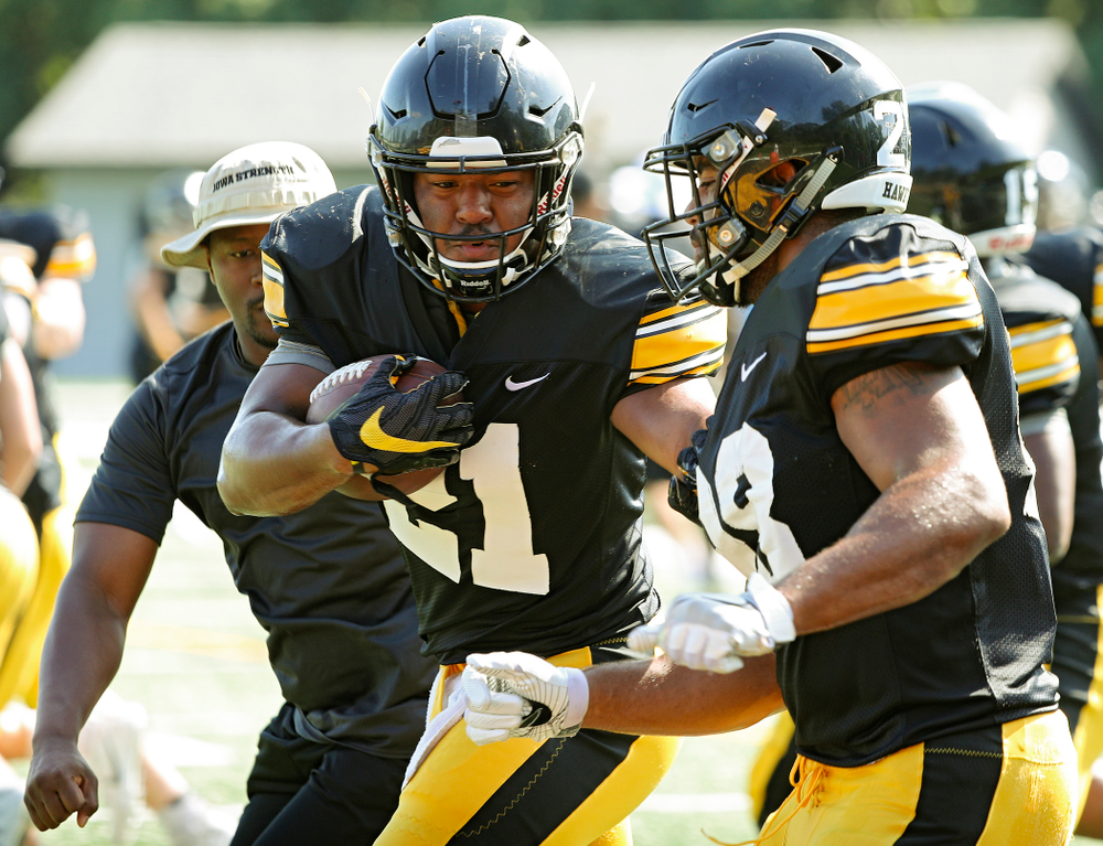 Iowa Hawkeyes running back Ivory Kelly-Martin (21) runs a drill between running backs coach Derrick Foster (left) and running back Toren Young (28) during Fall Camp Practice #5 at the Hansen Football Performance Center in Iowa City on Tuesday, Aug 6, 2019. (Stephen Mally/hawkeyesports.com)