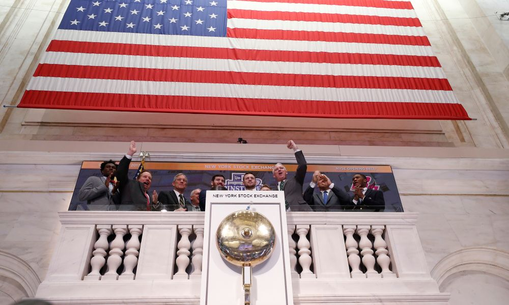 Iowa Hawkeyes linebacker Josey Jewell (43), defensive back Joshua Jackson (15), offensive lineman Sean Welsh (79) and head coach Kirk Ferentz ring the opening bell at the New York Stock Exchange Tuesday, December 26, 2017 in New York. (Brian Ray/hawkeyesports.com)