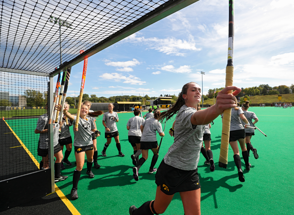 Iowa's Anthe Nijziel (6) grabs her stick with her teammates before the start of their match at Grant Field in Iowa City on Friday, Oct 4, 2019. (Stephen Mally/hawkeyesports.com)