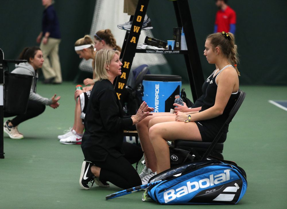 Head Coach Sasha Schmid talks with Ashleigh Jacobs and Sophie Clark as they play a doubles match against the Penn State Nittany Lions Sunday, February 24, 2019 at the Hawkeye Tennis and Recreation Complex. (Brian Ray/hawkeyesports.com)