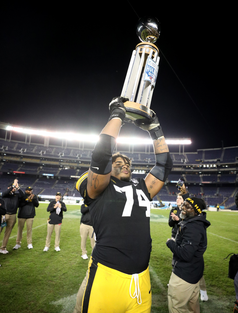 Iowa Hawkeyes offensive lineman Tristan Wirfs (74) celebrates with the Holiday Bowl trophy following their win against USC in the Holiday Bowl Friday, December 27, 2019 at San Diego Community Credit Union Stadium.  (Brian Ray/hawkeyesports.com)