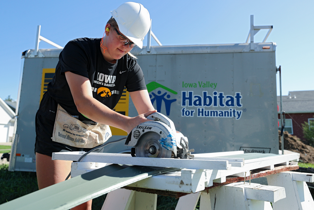 Iowa's Monika Czinano cuts a piece of siding as they work on a Habitat for Humanity Women Build project in Iowa City on Wednesday, Sep 25, 2019. (Stephen Mally/hawkeyesports.com)