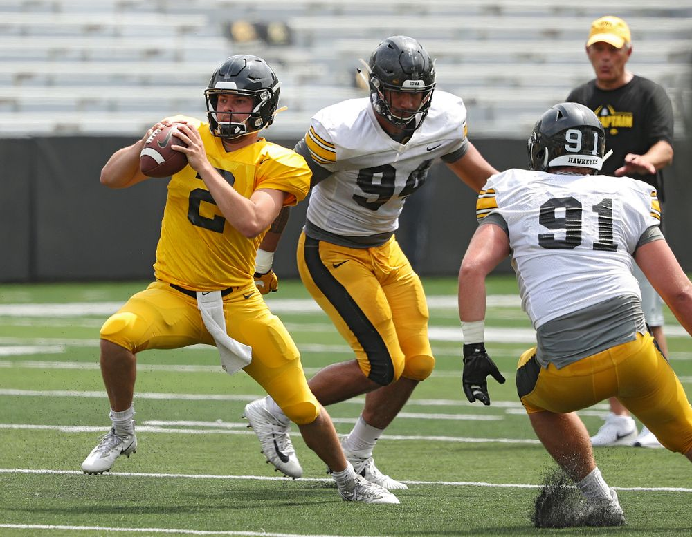 Iowa Hawkeyes quarterback Peyton Mansell (2) steps forward after he was caught between defensive end A.J. Epenesa (94) and defensive lineman Brady Reiff (91) during Fall Camp Practice No. 8 at Kids Day at Kinnick Stadium in Iowa City on Saturday, Aug 10, 2019. (Stephen Mally/hawkeyesports.com)