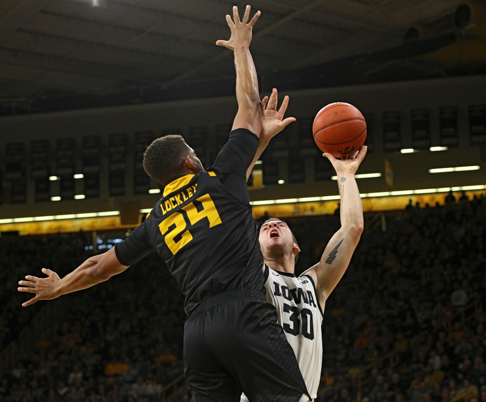 Iowa Hawkeyes guard Connor McCaffery (30) scores a basket around the arm of Kennesaw State Owls forward Bryson Lockley (24) during the first half of their their game at Carver-Hawkeye Arena in Iowa City on Sunday, December 29, 2019. (Stephen Mally/hawkeyesports.com)