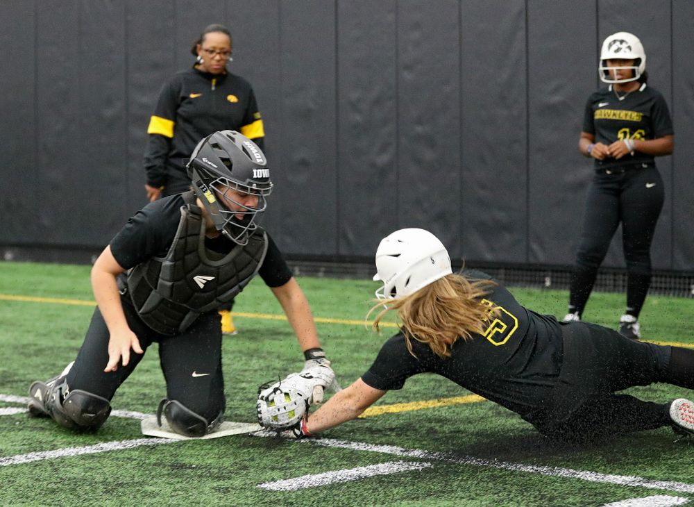 Iowa utility player/catcher Abby Lien (from left) tags infielder Sydney Owens (5) during practice at Iowa Softball Media Day at the Hawkeye Tennis and Recreation Complex in Iowa City on Thursday, January 30, 2020. (Stephen Mally/hawkeyesports.com)