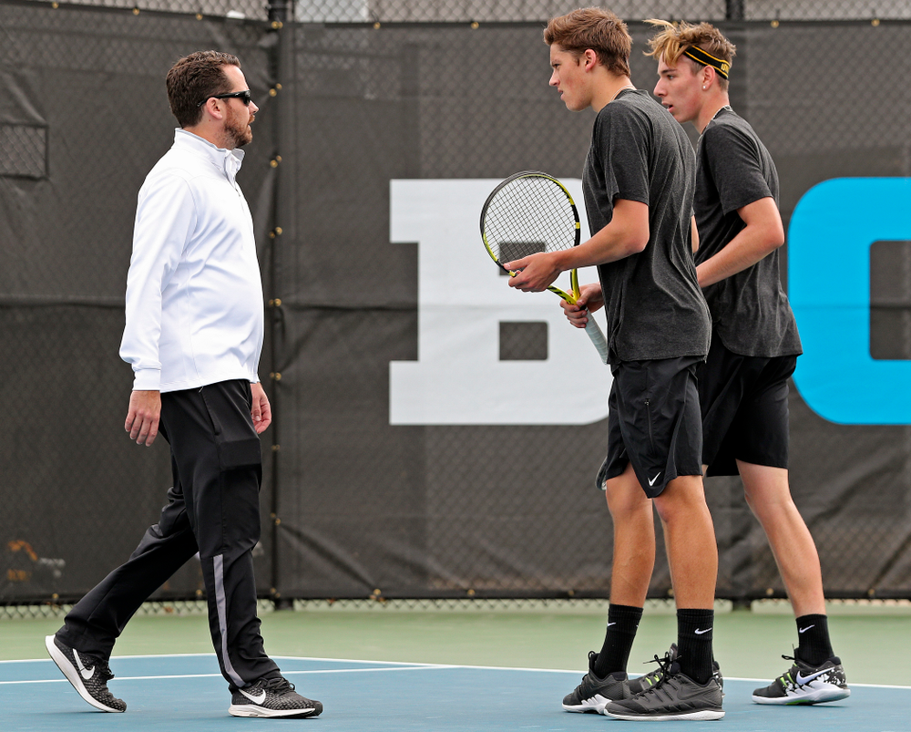 Iowa head coach Ross Wilson (from left) talks with Joe Tyler and Nikita Snezhko during a double match against Ohio State at the Hawkeye Tennis and Recreation Complex in Iowa City on Sunday, Apr. 7, 2019. (Stephen Mally/hawkeyesports.com)