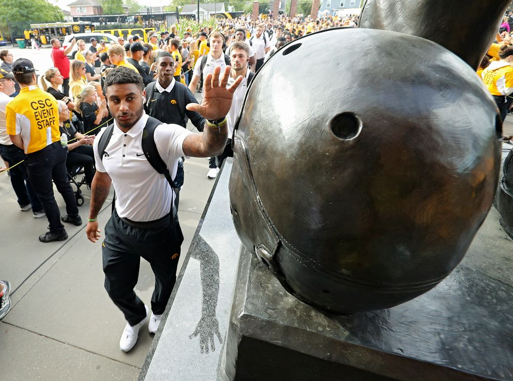 Iowa Hawkeyes defensive back Geno Stone (9) touches the helmet on the Nile Kinnick statue as the team arrives before their Big Ten Conference football game at Kinnick Stadium in Iowa City on Saturday, Sep 7, 2019. (Stephen Mally/hawkeyesports.com)